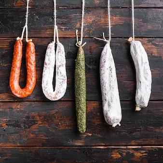 Spanische trockenwürste hängen von einem gestell am markt auf altem holztisch, quadratisches format