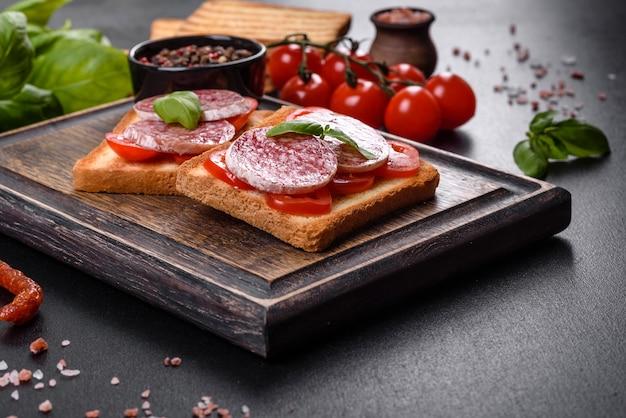 Spanische trockenwurstsalami auf dunklem betonhintergrund. zubereitung von leckeren frischen sandwiches