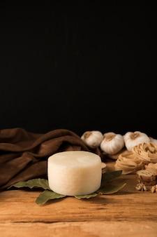 Spanischer manchego-käse, lorbeerblätter, rohe teigwaren und knoblauchknollen auf holztisch