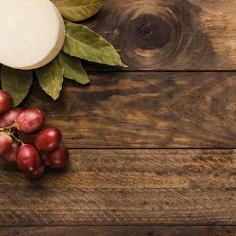 Spanischer manchego; rote saftige trauben und lorbeerblätter und holzoberfläche