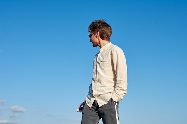 Spanischer mann in einem beigen hemd, das zur seite mit einem telefon in der einen hand und der anderen in seiner tasche auf klarem himmel schaut