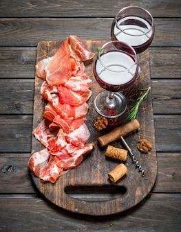 Spanischer schinken mit einem glas rotwein. auf einem hölzernen hintergrund.