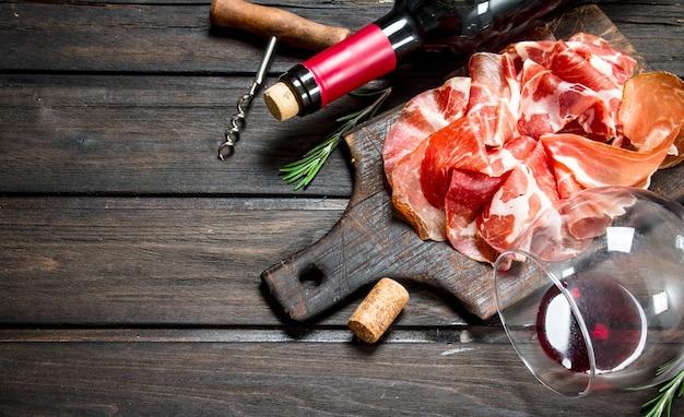 Spanischer schinken mit einem glas rotwein. auf einem holz.
