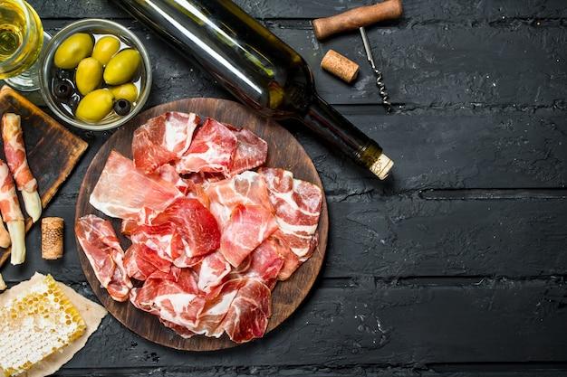 Spanischer schinken mit rotwein und grissini auf rustikalem tisch.