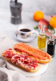 Spanischer tomaten-schinken-toast, traditionelles frühstück oder mittagessen mit kaffee
