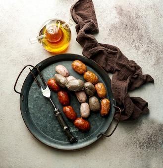 Spanisches essen - spanische würstchen auf dem schneidebrett - butifarra blanca, chorizo, morcilla de cebolla