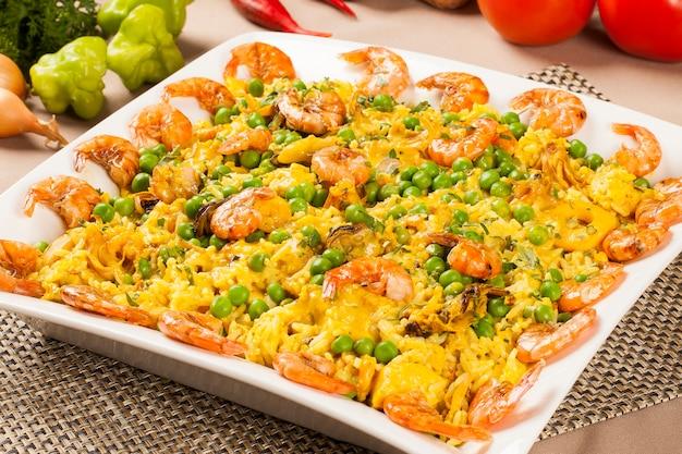 Spanisches gericht paella mit meeresfrüchten, garnelen, tintenfisch, reis, safran, traditionelles leckeres abendessen