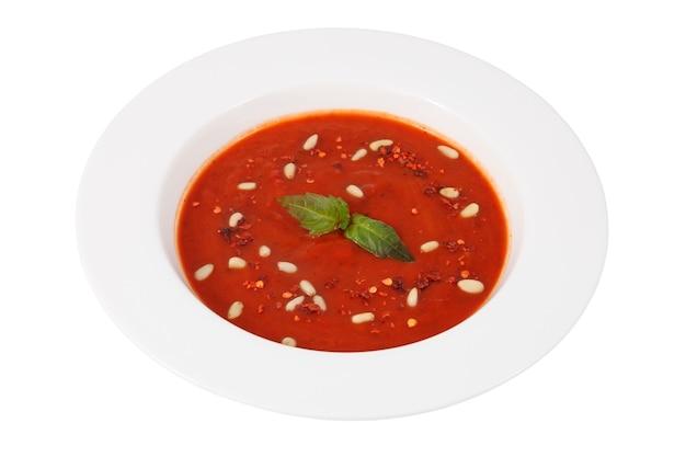Spanisches gericht von gazpacho, kalte tomatensuppe mit bohnen in der weißen tiefen platte lokalisiert auf weißem hintergrund.