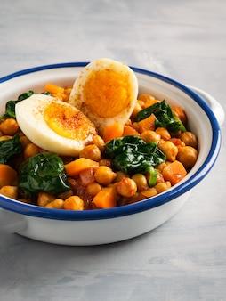 Spanisches kichererbsen- und spinateintopfgericht mit eiern auf hellgrauem hintergrund. spanische küche.