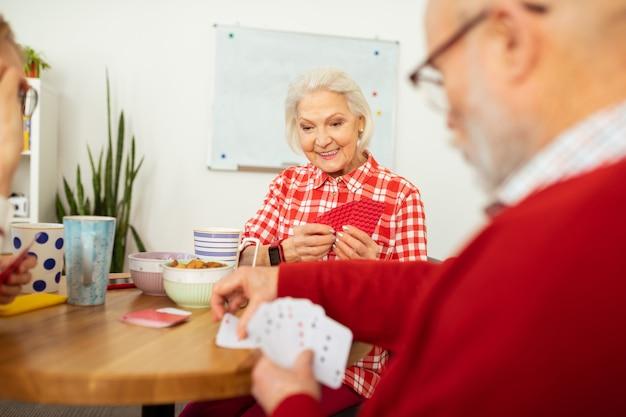 Spannende unterhaltung. angenehme ältere frau, die ihre karten beim spielen mit ihrem freund hält