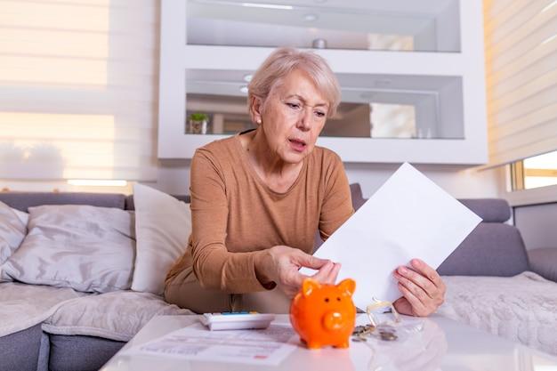 Spar-, geld-, rentenversicherungs-, alters- und personenkonzept - hand der älteren frau, die münze in sparschwein legt. ältere alte frau schockiert über die rechnungen, die sie erhält, entsetzt und nach luft schnappend