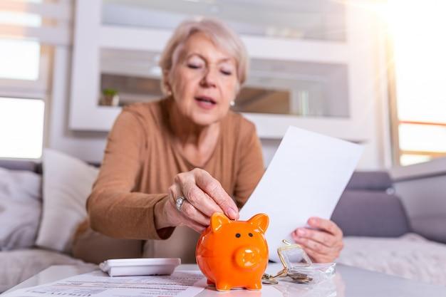 Spar-, geld-, rentenversicherungs-, alters- und personenkonzept - hand der älteren frau, die münze in sparschwein legt. glückliche reife frau, die münze im sparschwein berechnet