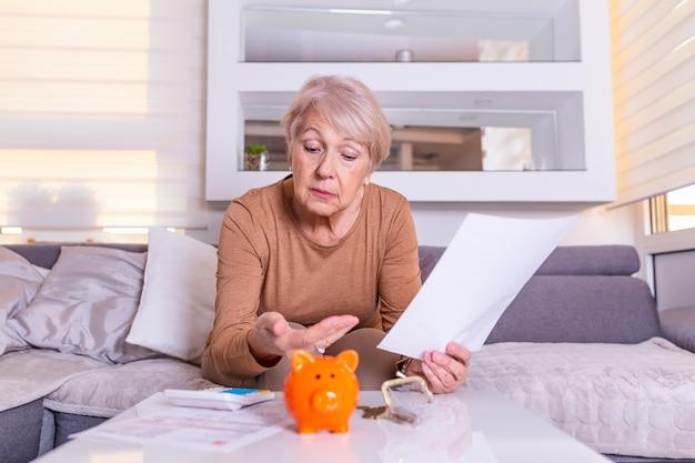 Spar-, geld-, rentenversicherungs-, alters- und personenkonzept - hand der älteren frau, die münze in sparschwein legt. reife frau, die münze im sparschwein berechnet