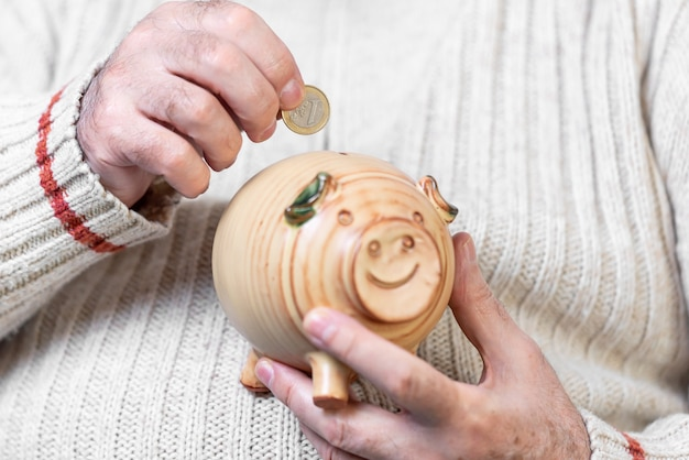 Spar-, geld-, rentenversicherungs-, alters- und personenkonzept - nahaufnahme der hand des älteren mannes, die münze in sparschwein legt.
