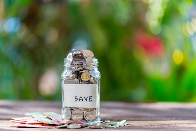Spareinlagenmünzen in einer klarglasflasche, auf einem bretterboden mit bokeh im hintergrund.