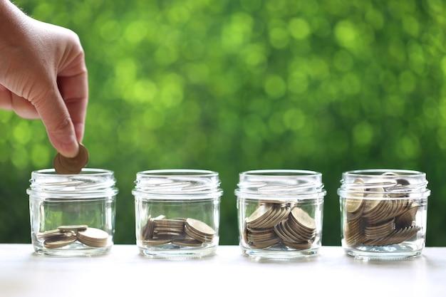 Sparen für die vorbereitung in zukunft und geschäftsinvestitionskonzept, frauenhand, die eine münze in die glasflasche auf grünem hintergrund, finanzen setzt