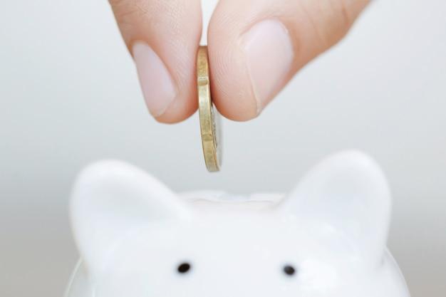 Sparen, hand, die goldene münze in sparschwein sparbüchse weiß setzt.
