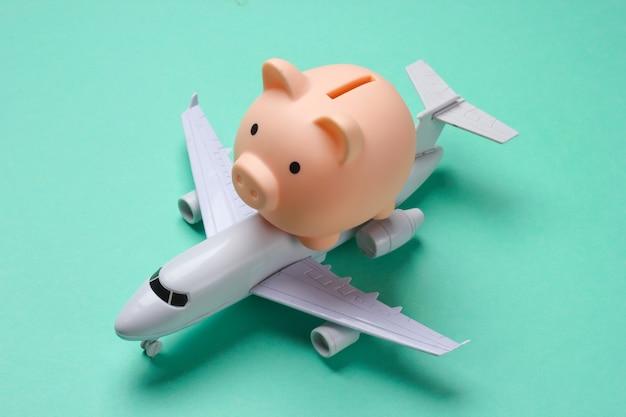 Sparen sie für flugreisen. sparschwein mit spielzeugflugzeug auf blau.