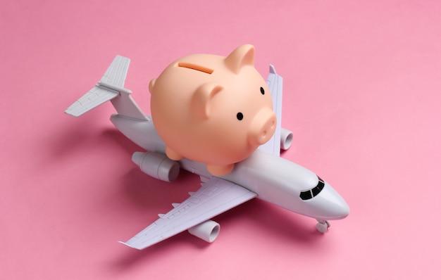 Sparen sie für flugreisen. sparschwein mit spielzeugflugzeug auf rosa.