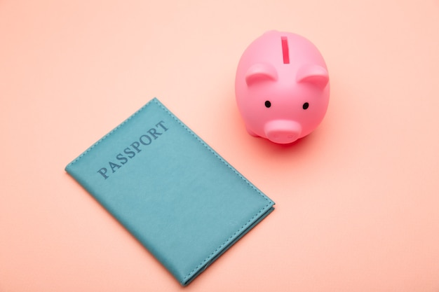 Sparen sie für unterwegs. sparschwein mit pass auf rosa hintergrund. draufsicht. flach liegen