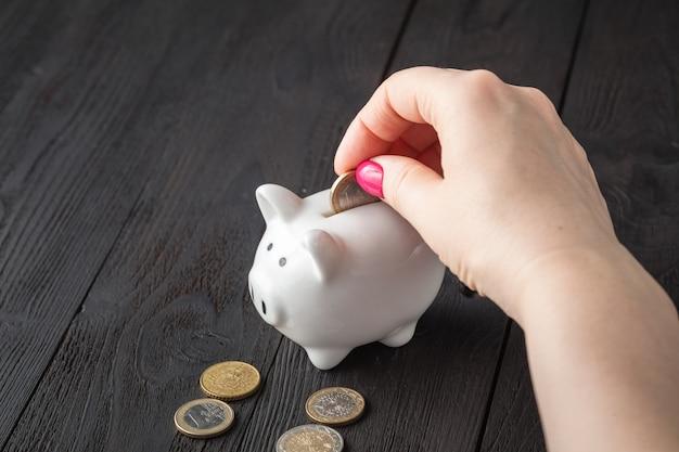 Sparen sie geld konzept, sparschwein in einer menschlichen hand