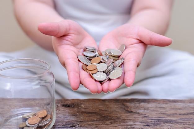 Sparen sie geld und account banking für das finanzkonzept. hand mit münze auf unscharfem hintergrund