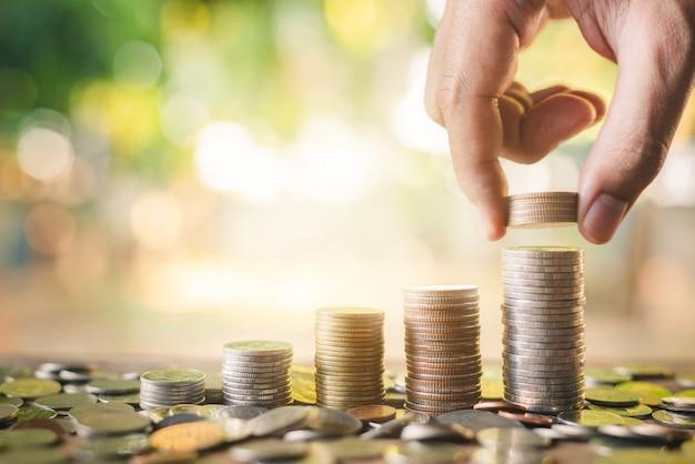 Sparen sie geldkonzept mit der hand, welche die münze auf wachsendes geschäft des münzenstapels setzt