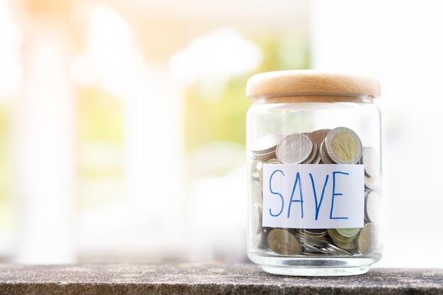 Sparen sie geldkonzept mit münze in der flasche auf abstraktem bokeh hintergrund-kopienraum