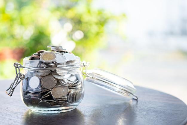 Sparen sie geldmünzen im grasglas, geschäftsfinanzierungsinvestitionskonzept.