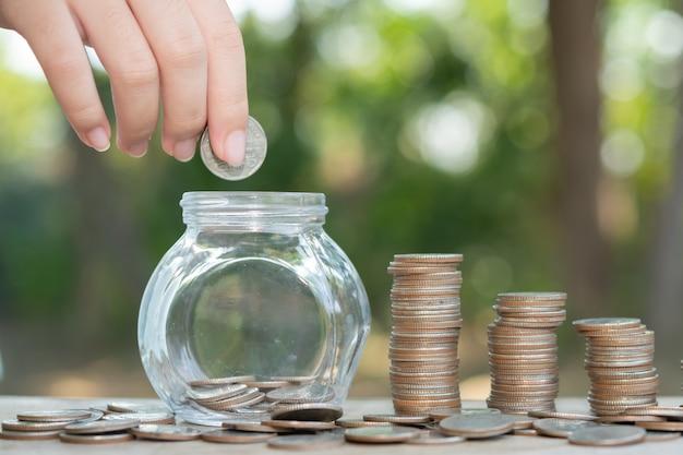 Sparen von geldkonzept von männlicher hand voreingestellt, das geldmünzenstapel wachsendes geschäft setzt. ordne münzen mit den händen zu haufen an, begnüge dich mit geld.