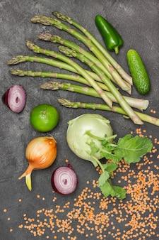 Spargel, gurken, limette und kohlrabi, zwiebeln und rote linsen auf dem tisch. schwarzer hintergrund. flach liegen.