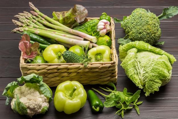 Spargel, paprika und gurken im rattankorb. wirsing, brokkoli und wirsing auf dem tisch. hölzerner hintergrund. ansicht von oben