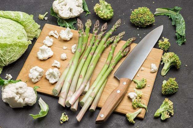 Spargel und küchenmesser auf schneidebrett. kohl auf dem tisch. schwarzer hintergrund. flach legen