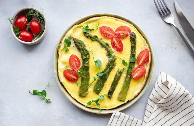 Spargel und tomaten frittata mit microgreens auf grauem tisch italienische küche table