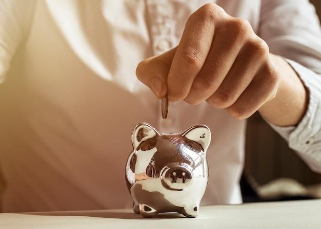 Spargeldkonzept mit männlicher hand, die eine münze in sparschwein setzt