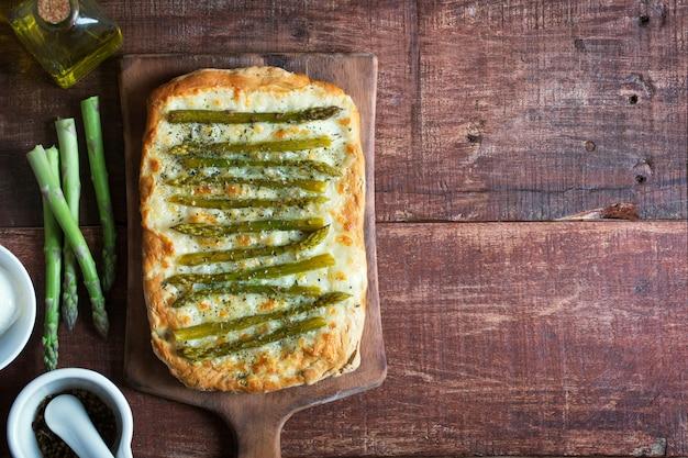 Spargelgrüne pizza mit kräutern und mozzarella-hintergrund
