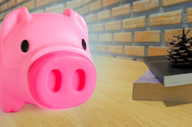 Sparschwein auf dem oberen tisch mit lehrbüchern.