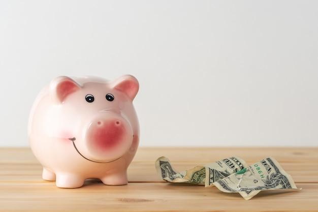 Sparschwein auf einem holztisch mit zerknitterter dollarbanknote