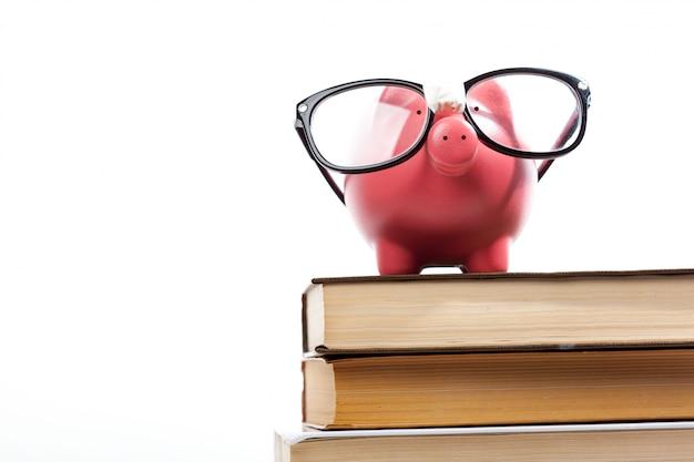 Sparschwein auf einem stapel des buchkonzeptes der ausbildungskosten