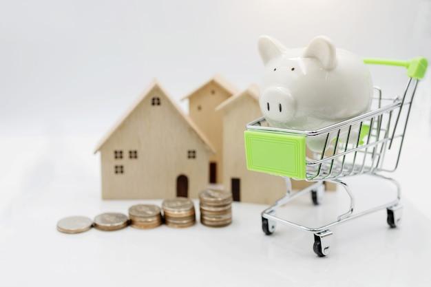 Sparschwein auf einkaufswagen mit münzenstapel und haus. konzept der investition in wohnraum.