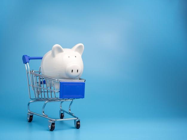 Sparschwein auf einkaufswagenwagen auf blau