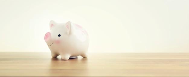 Sparschwein auf holztisch. ein sparsames geld für das zukünftige investitionskonzept.