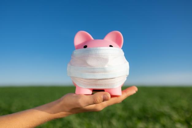 Sparschwein, das schutzmaske in der hand gegen frühlingsgrünfeld und blaue himmelsoberfläche trägt