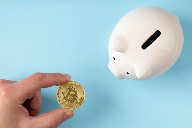 Sparschwein der draufsicht mit person, die eine bitcoin hält