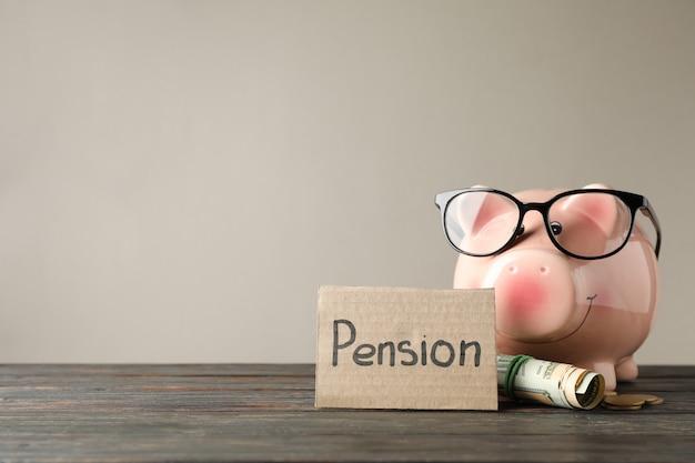 Sparschwein, geld und inschrift pension gegen graue oberfläche