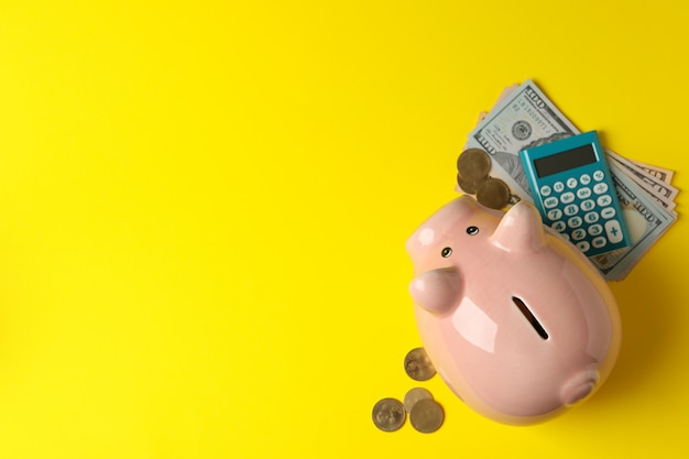 Sparschwein, geld und taschenrechner auf gelber draufsicht