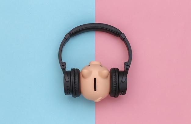 Sparschwein hört stereokopfhörer auf blau-rosa pastellhintergrund. ansicht von oben