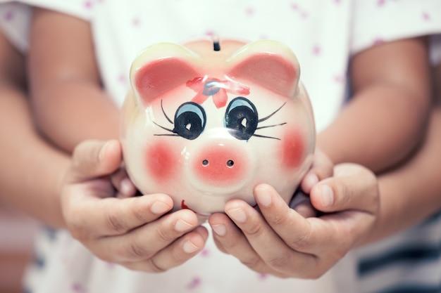 Sparschwein in den kinderkinder- und -mutterhänden