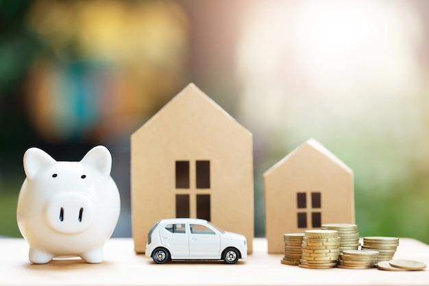 Sparschwein, kleines spielzeugauto, geldmünzen in verschiedenen positionen aufeinander gestapelt, haus im papiermodell auf dem holztisch.