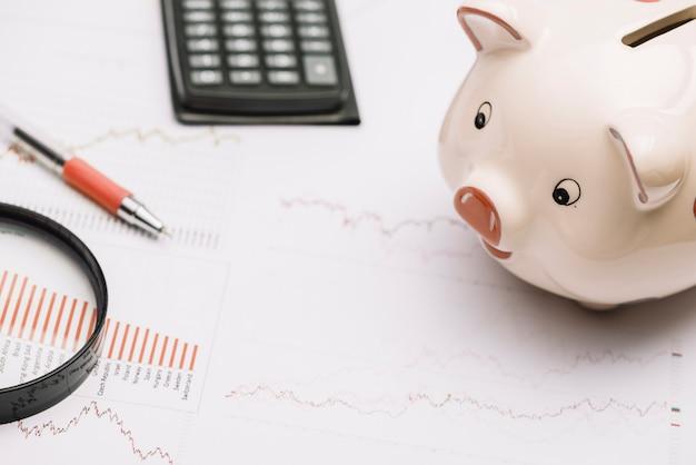 Sparschwein; lupe; taschenrechner und stift auf aktienmarktdiagramm